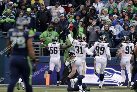 St. Louis Rams' Akeem Ayers (56) raises his arms as he scores on a fumble recovery against the Seattle Seahawks in the first half of an NFL football game, in Seattle