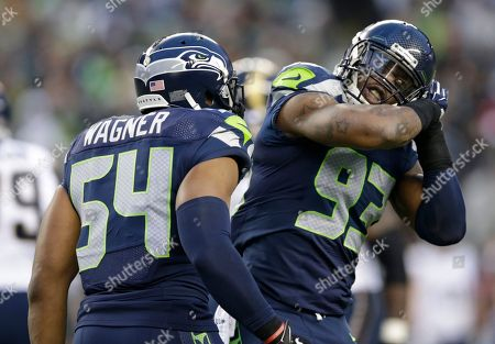 Seattle Seahawks defensive end O'Brien Schofield, right, makes a sleeping motion as he celebrates a play against the St. Louis Rams with Bobby Wagner (54) in the second half of an NFL football game, in Seattle