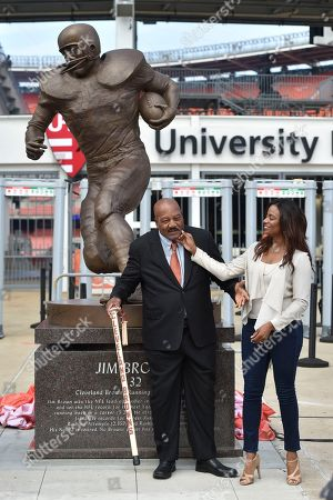 Jim Brown, Monique Brown. Former Cleveland Browns Pro Football Hall of Famer Jim Brown, center, and his wife Monique, right, is honored with a ceremony and statue outside FirstEnergy Stadium before an NFL football game against the Baltimore Ravens, in Cleveland