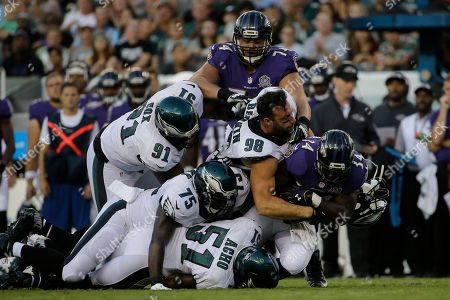 Philadelphia Eagles' Connor Barwin (98) looses his helmet as he combines with Emmanuel Acho (51), Vinny Curry (75) and Fletcher Cox (91) to tackle Baltimore Ravens' Lorenzo Taliaferro (34) during the first half of a preseason NFL football game, in Philadelphia