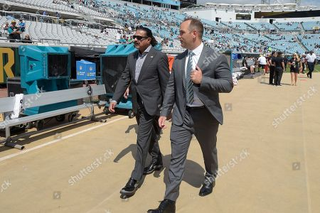 Jacksonville Jaguars owner Shad Khan, left, and general manager David Caldwell walk on the field before an NFL football game against the Baltimore Ravens in Jacksonville, Fla