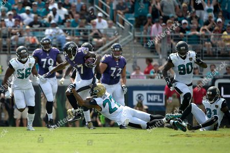 Mike Wallace, Dwayne Gratz. Baltimore Ravens receiver Mike Wallace (17) is tackled by Jacksonville Jaguars cornerback Dwayne Gratz (27) after catching a pass during the first half of an NFL football game in Jacksonville, Fla