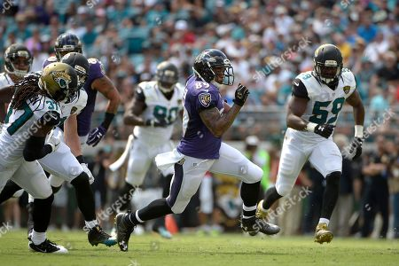 Baltimore Ravens wide receiver Steve Smith (89) runs after catching a pass between Jacksonville Jaguars strong safety Johnathan Cyprien (37) and linebacker Arthur Brown (59) during the first half of an NFL football game in Jacksonville, Fla