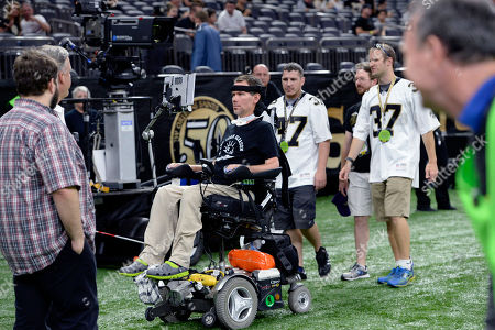 Former New Orleans Saints Steve Gleason rides in his wheelchair on the sideline before an NFL football game against the Baltimore Ravens in New Orleans