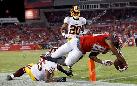 Solomon Patton, Adam Hayward, Richard Crawford. Tampa Bay Buccaneers wide receiver Solomon Patton (86) dives past Washington Redskins outside linebacker Adam Hayward (55) and cornerback Richard Crawford (20) to score on a 25-yard touchdown reception during the third quarter of an NFL preseason football game, in Tampa, Fla