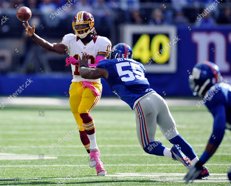 Robert Griffin III, Keith Rivers. Washington Redskins quarterback Robert Griffin III looks to pass as he is pressured by New York Giants linebacker Keith Rivers (55) during the second half of an NFL football game, in East Rutherford, N.J