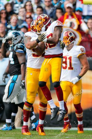 Jason Hatcher, Dashon Goldson. Washington Redskins defensive end Jason Hatcher (97) reacts after making a tackle with free safety Dashon Goldson (38) against the Carolina Panthers during an NFL game at Bank of America Stadium in Charlotte, N.C. on
