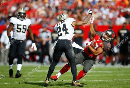 Kyle Wilson, Doug Martin. New Orleans Saints defensive back Kyle Wilson (24) throws a cheap shot to Tampa Bay Buccaneers running back Doug Martin (22), getting a personal foul during an NFL football game, in Tampa, Fla