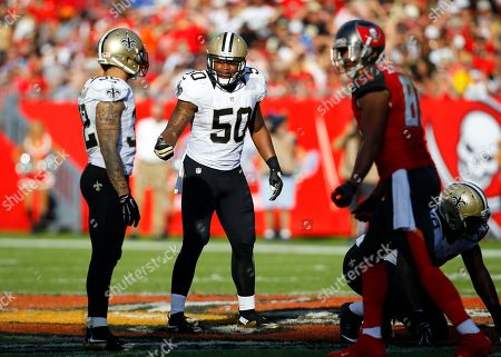 Stock Image of Stephone Anthony, Kenny Vaccaro. New Orleans Saints middle linebacker Stephone Anthony (50) talk to teammate strong safety Kenny Vaccaro (32) before the snap against the Tampa Bay Buccaneers during an NFL football game, in Tampa, Fla
