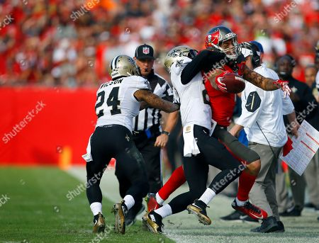 Mike Evans, Brian Dixon, Kyle Wilson. Tampa Bay Buccaneers wide receiver Mike Evans (13) reaches the ball forward while being taken out of bounds by New Orleans Saints defensive back Brian Dixon (20) and defensive back Kyle Wilson (24) and during an NFL football game, in Tampa, Fla