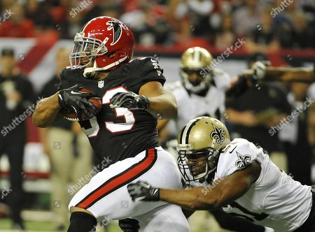 Michael turner, Jonathan Vilma. Atlanta running back Michael Turner (33) tries to break away from New Orleans Saints outside linebacker Jonathan Vilma (51) during the first half of an NFL football game, in Atlanta