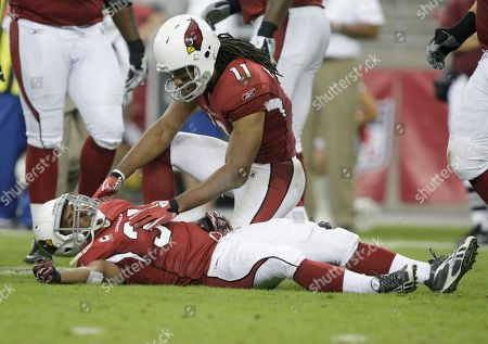 Larry Fitzgerald, Jason Wright. Arizona Cardinals wide receiver Larry Fitzgerald (11) checks on teamamte Jason Wright during the third quarter of an NFL football game, in Glendale, Ariz