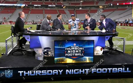 Stock Image of Rich Eisen, Dion Sanders, Steve Mariucci, Russell Wilson, Kurt Warner, Michael Irvin. The NFL Network Thursday Night Football live crew from left, Rich Eisen, Dion Sanders, Steve Mariucci, Seattle Seahawks quarterback Russell Wilson, Kurt Warner and Michael Irvin talk after a NFL football game against the Arizona Cardinals and the Seattle Seahawks, in Glendale, Ariz