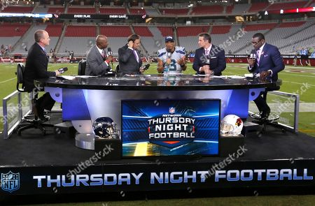 Rich Eisen, Dion Sanders, Steve Mariucci, Russell Wilson, Kurt Warner, Michael Irvin. The NFL Network Thursday Night Football live crew from left, Rich Eisen, Dion Sanders, Steve Mariucci, Seattle Seahawks quarterback Russell Wilson, Kurt Warner and Michael Irvin talk after a NFL football game against the Arizona Cardinals and the Seattle Seahawks, in Glendale, Ariz
