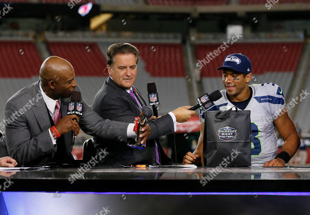 Dion Sanders, Russell Wilson, Steve Mariucci. The NFL Network Thursday Night Football live crew Steve Mariucci, center, and Dion Sanders, right, talk with the player of the game, Seattle Seahawks' Russell Wilson, left, after an NFL football game against the Arizona Cardinals and the Seattle Seahawks, in Glendale, Ariz
