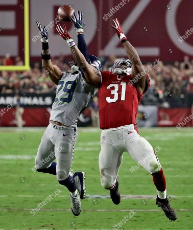Seattle Seahawks free safety Earl Thomas (29) breaks up a pass intended for Arizona Cardinals running back David Johnson (31) during the first half of a football game, in Glendale, Ariz