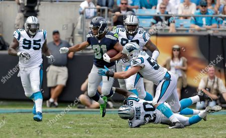 Doug Baldwin, D.J. Moore, Luke Kuechly, Charles Johnson, Chase Blackburn. Seattle Seahawks' Doug Baldwin (89) keeps his feet as he jumps through the tackle attempts of Carolina Panthers' D.J. Moore (20) and Luke Kuechly (59) as Carolina Panthers' Charles Johnson (95) and Chase Blackburn (93) give chase during the second half of an NFL football game in Charlotte, N.C., . Seattle won 12-7