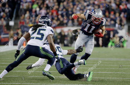 Richard Sherman, Earl Thomas, Julian Edelman. Seattle Seahawks cornerback Richard Sherman (25) and free safety Earl Thomas (29), center, try to stop New England Patriots wide receiver Julian Edelman (11) during the first half of an NFL football game, in Foxborough, Mass