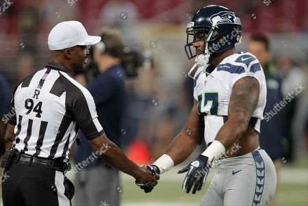 Referee Mike Carey (94) is greeted by Seattle Seahawks wide receiver Braylon Edwards before an NFL football game against the St. Louis Rams, in St. Louis