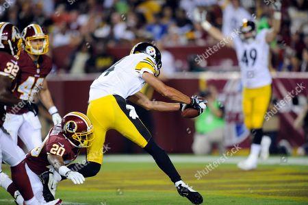 Derek Moye, Richard Crawford. Pittsburgh Steelers wide receiver Derek Moye (14) scores a touchdown in spite of the efforts of Washington Redskins cornerback Richard Crawford (20) during the second half of an NFL preseason football game, in Landover, Md