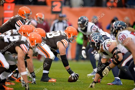 Stock Image of Cleveland Browns center Nick McDonald, center, prepares to snap the ball to quarterback Brian Hoyer in the fourth quarter of an NFL football game against the Houston Texans, in Cleveland