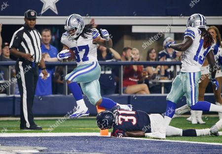 Gus Johnson, Charles James. Dallas Cowboys running back Gus Johnson (37) scores over Houston Texans defensive back Charles James (31) during the second half of a preseason NFL football game, in Arlington, Texas