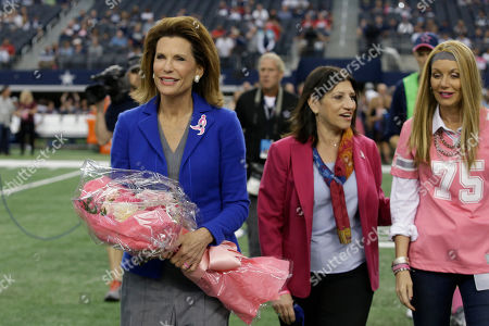 Nancy Brinker, founder and chair of Susan G. Komen For the Cure, left, walks on the field for a presentation recognizing Breast Cancer Awareness month before an NFL football game between the Dallas Cowboys and the Houston Texans, in Arlington, Texas