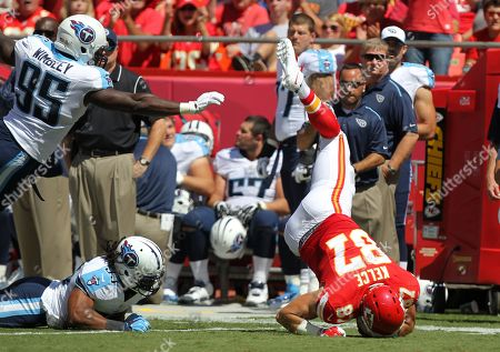 Travis Kelce, Michael Griffin. Kansas City Chiefs tight end Travis Kelce (87) is upended by Tennessee Titans safety Michael Griffin (33) and linebacker Kamerion Wimbley (95) in the first half of an NFL football game in Kansas City, Mo
