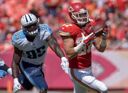 Travis Kelce, Kamerion Wimbley. Kansas City Chiefs tight end Travis Kelce (87) makes a catch in front of Tennessee Titans linebacker Kamerion Wimbley (95) during their NFL football game in Kansas City, Mo