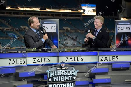 Bill Cowher, Phil Simms. Thursday Night Football sportscaster Bill Cowher, left, and Phil Simms broadcast from the set on the field before an NFL football game between the Jacksonville Jaguars and the Tennessee Titans in Jacksonville, Fla
