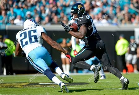 Jordan Babineaux, Justin Blackmon. Jacksonville Jaguars wide receiver Justin Blackmon (14) runs after making a catch in front of Tennessee Titans strong safety Jordan Babineaux (26) during the first half of an NFL football game in Jacksonville, Fla