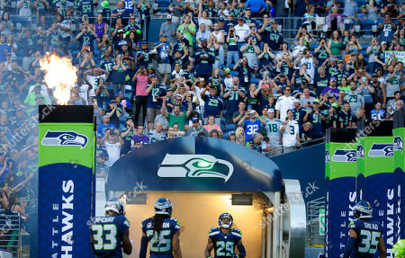 Fans cheer as Seattle Seahawks players Kelcie McCray (33), Richard Sherman (25) and Earl Thomas take the field for a preseason NFL football game against the Minnesota Vikings, in Seattle
