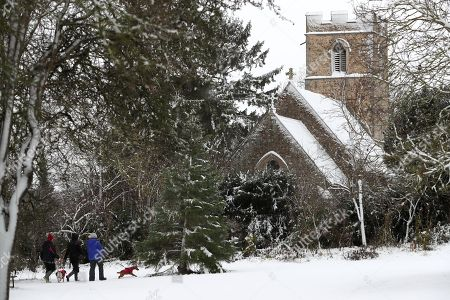 Dog walkers make their way through the snow near the church of St Michael and All Angels in Caldecote Cambridgeshire, after heavy overnight snow fall in the county.