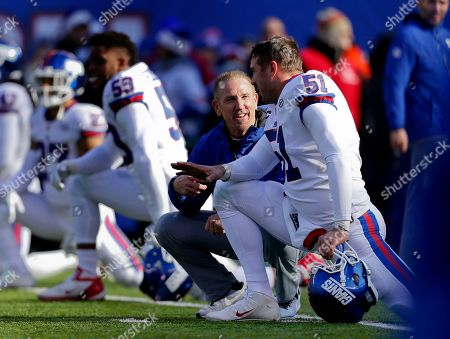 New York Giants interim head coach Steve Spagnuolo, left, talks with long snapper Zak DeOssie (51) before an NFL football game against the Dallas Cowboys, in East Rutherford, N.J