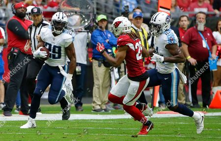Tennessee Titans running back DeMarco Murray (29) runs with the ball as Titans wide receiver Corey Davis (84) looks to block Arizona Cardinals defensive back Tramon Williams (25) during the first half of an NFL football game, Sunday, Dec.10, 2017, in Glendale, Ariz