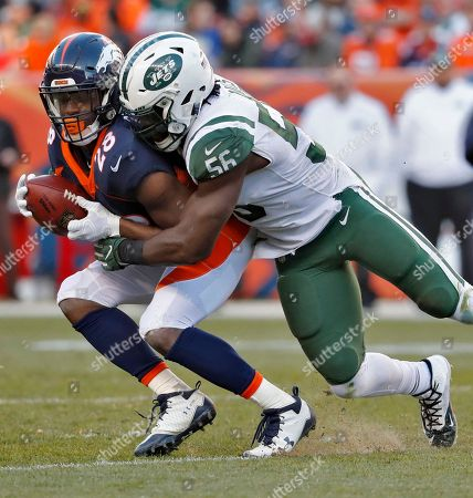 Denver Broncos running back Jamaal Charles (28) is hit by New York Jets inside linebacker Demario Davis (56) during the first half of an NFL football game, in Denver