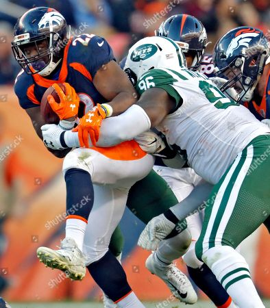Denver Broncos running back C.J. Anderson (22) is hit by New York Jets defensive end Muhammad Wilkerson (96) during the second half of an NFL football game, in Denver