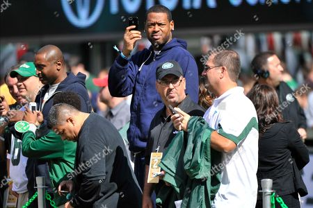 New York Knicks Marcus Camby, center, watches the New York Jets warm up before an NFL football against the San Francisco 49ers, in East Rutherford, N.J
