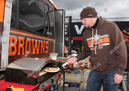 Mark Shaw cooks a pizza before an NFL football game between the Denver Broncos and the Cleveland Browns, in Cleveland