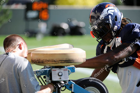 David Burton. Denver Broncos safety David Bruton tries to fix the pass machine during NFL football training camp at Broncos headquarters in Englewood, Colo