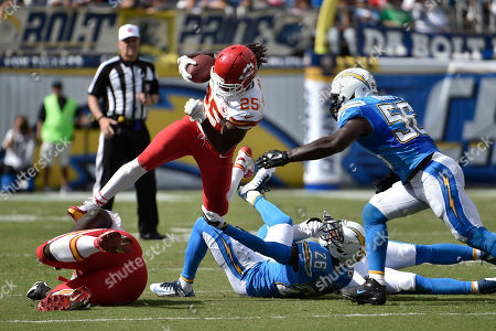 Kansas City Chiefs running back Jamaal Charles leaps over San Diego Chargers cornerback Brandon Flowers (26) and inside linebacker Andrew Gachkar, right, during the first half of an NFL football game, in San Diego