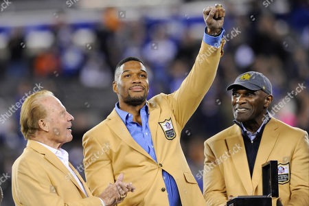 Stock Image of Pro Football Hall of Fame defensive end Michael Strahan, center, receives his Hall of Fame Ring of Excellence as Frank Gifford, left, and Harry Carson, right, watch him during a halftime ceremony of an NFL football game between the New York Giants and the Indianapolis Colts, in East Rutherford, N.J