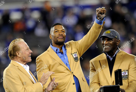 Pro Football Hall of Fame defensive end Michael Strahan, center, receives his Hall of Fame Ring of Excellence as Frank Gifford, left, and Harry Carson, right, stand near during a halftime ceremony of an NFL football game between the New York Giants and the Indianapolis Colts, in East Rutherford, N.J