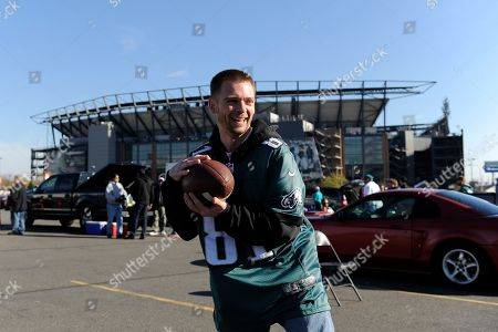 Stock Image of Jeff Baker, of Bensalem, Pa., plays catch outside of Lincoln Financial Field before an NFL football game between the Philadelphia Eagles and the Miami Dolphins, in Philadelphia