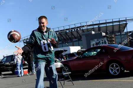 Stock Picture of Jeff Baker, of Bensalem, Pa., plays catch outside of Lincoln Financial Field before an NFL football game between the Philadelphia Eagles and the Miami Dolphins, in Philadelphia
