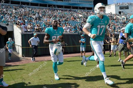Greg Jennings, Ryan Tannehill. Miami Dolphins wide receiver Greg Jennings (85) and quarterback Ryan Tannehill (17) run onto the field prior to the first half of an NFL football game against the Jacksonville Jaguars in Jacksonville, Fla