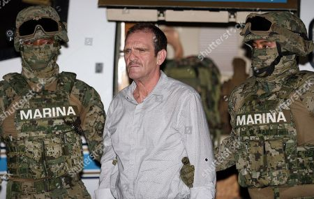 """Stock Image of In this photo provided by Mexico's Attorney General's Office, Hector """"El Guero"""" Palma is escorted to a helicopter in handcuffs by Mexican marines at a federal hangar in Mexico City, . Palma, one of the founders of the Sinaloa Cartel, returned to his native Mexico after serving almost a decade in a U.S. prison and was immediately transported to another maximum-security lockup where he will await trial for two murders"""