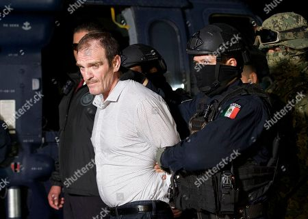 """In this photo provided by the Mexican Attorney General's Office, Hector """"El Guero"""" Palma, is escorted in handcuffs from a helicopter at a federal hanger in Mexico City, . Palma, one of the founders of the Sinaloa Cartel, returned to his native Mexico after serving almost a decade in a U.S. prison and was immediately transported to another maximum-security lockup where he will await trial for two murders"""