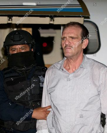 """Stock Picture of In this photo provided by Mexico's attorney general, Hector """"El Guero"""" Palma is escorted in handcuffs to a helicopter by Federal Police at a federal hangar in Mexico City, . Drug lord Hector """"El Guero"""" Palma, one of the founders of the Sinaloa Cartel, returned to his native Mexico after serving almost a decade in a U.S. prison and was immediately transported to another maximum-security lockup where he will await trial for two murders"""