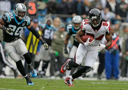 Stock Picture of Roddy White, Antoine Cason. Atlanta Falcons' Roddy White (84) runs after a catch as Carolina Panthers' Antoine Cason (20) pursues in the first half of an NFL football game in Charlotte, N.C